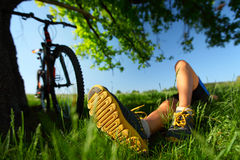 Relax. Young lady relaxing on a green meadow after cycling. Focus on a foot Stock Photo