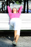 Relax young woman sits on a bench Royalty Free Stock Photography