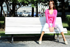 Relax young woman sits on a bench Royalty Free Stock Photo