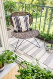 Relax zone on a balcony with a chair, rug and plants. Top view, real photo royalty free stock image