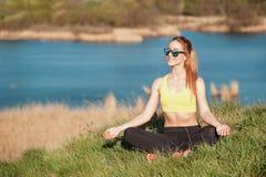 Relaxamento após a formação A moça atrativa no sportwear elegante e os óculos de sol que sentam-se na grama e que fazem a meditaç Imagens de Stock Royalty Free