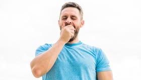 Relaxamento ap?s a forma??o atleta do homem no tshirt azul do esporte Forma do Sportswear homem muscular de bocejo com barba slee imagens de stock