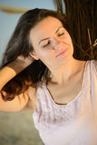 Relaxamento bonito da mulher, apreciando o por do sol na praia Fotos de Stock Royalty Free