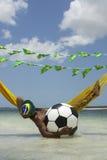 Relaxamento brasileiro com futebol do futebol na rede da praia foto de stock royalty free