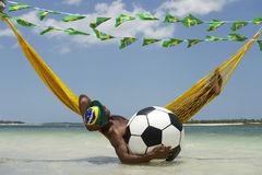 Relaxamento brasileiro com futebol do futebol na rede da praia imagens de stock