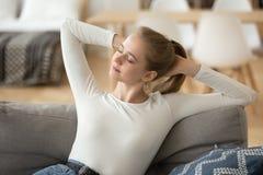 Relaxamento calmo feliz da mulher, esticando no sofá confortável em casa foto de stock royalty free