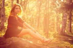 Relaxamento da jovem mulher exterior na floresta ensolarada Imagem de Stock