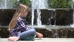 Relaxamento de assento da criança no parque por gotas de observação da água da fonte, menina 4K exterior filme