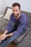 Relaxamento de assento do homem farpado em um sofá Fotos de Stock Royalty Free