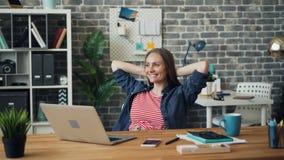Relaxamento de sorriso da menina alegre no trabalho após ter usado o laptop no escritório filme