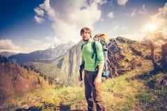 Relaxamento do viajante do homem novo exterior com as montanhas no fundo Fotos de Stock Royalty Free