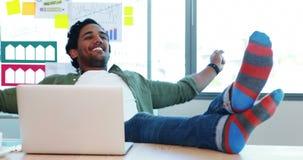 Relaxamento executivo masculino com pés acima na mesa filme