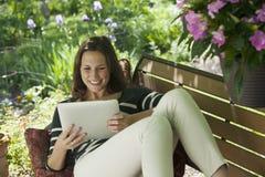 Relaxamento fora de ler uma tabuleta digital Imagens de Stock Royalty Free
