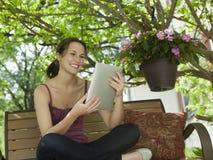 Relaxamento fora de ler uma tabuleta digital Foto de Stock Royalty Free