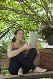 Relaxamento fora de ler uma tabuleta digital Imagem de Stock Royalty Free