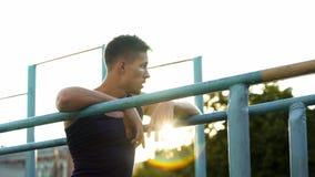 Relaxamento masculino considerável após a formação em barras transversais no por do sol, passatempo do esporte fotos de stock