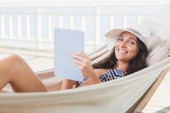 Relaxamento moreno bonito em uma rede e utilização do PC da tabuleta fotografia de stock royalty free