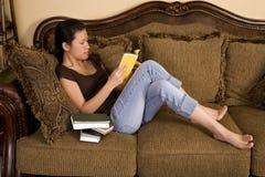 Relaxamento na leitura do sofá imagem de stock