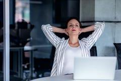 Relaxamento no lugar de funcionamento Jovem mulher atrativa que guarda as mãos atrás da cabeça e que mantém os olhos fechados ao  fotografia de stock