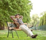 Relaxamento superior em um banco de madeira imagem de stock royalty free