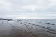 Relaxando e dome as ondas de acalmação que fluem em uma praia em um dia nublado sombrio Imagem de Stock
