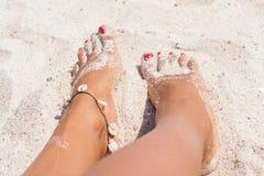 Relaxando em uma praia, com seus pés na areia Foto de Stock Royalty Free
