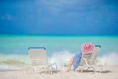 Relaxar e apreciar em férias de verão, mulher que encontra-se sobre sunbed na praia Imagens de Stock Royalty Free