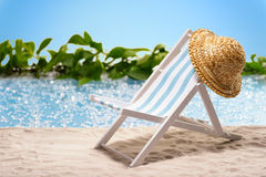 Relaxation à la plage avec le canapé du soleil et chapeau de soleil devant une lagune bleue Images stock