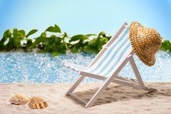 Relaxation à la plage avec le canapé du soleil et chapeau de soleil devant une lagune bleue Photographie stock libre de droits
