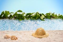 Relaxation à la plage avec le chapeau de soleil et coquilles devant une lagune bleue photo libre de droits