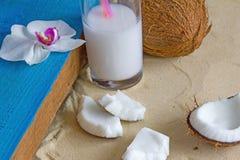 Relaxation à la plage avec les noix de coco, le lait de noix de coco et l'orchidée Photos libres de droits