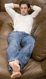 Relaxation. A young attractive man resting on the couch Stock Photos
