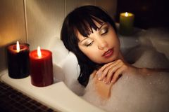 Relaxation. The girl lies in a bath with foam, candles burn stock image