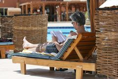 Relaxation. The man has a rest near swimming pool Royalty Free Stock Images