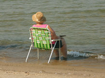 Relaxation. Lady sits on shore of beach Stock Photo