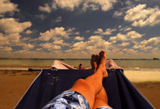 Relaxation. Relaxing at the beach on the portable hammock on one sunny afternoon Royalty Free Stock Images