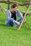 Relaxation. Young woman relaxing on a green field near a wooden fence Stock Photo