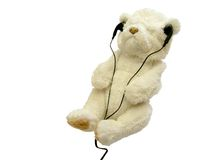 Relaxation. White teddy bear with earphones isolated on white royalty free stock images