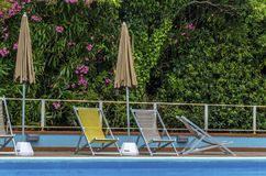 View of a swimming pool with deckchairs and sun umbrellas royalty free stock image