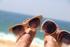 Relaxation on the beach. Summer holiday - funny female feet in sunglasses Royalty Free Stock Photography