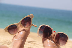 Relaxation on the beach. Summer holiday - funny female feet in sunglasses Royalty Free Stock Photo