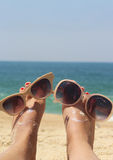 Relaxation on the beach. Summer holiday - funny female feet in sunglasses Royalty Free Stock Images