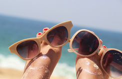 Relaxation on the beach. Summer holiday - funny female feet in sunglasses Stock Photography