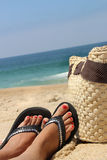 Relaxation on the beach. And female feet Stock Photography
