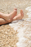 Relaxation on beach, detail of male feet Stock Images