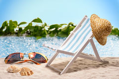 Relaxation at the beach with sun lounger and sunhat in front of a blue lagoon Royalty Free Stock Photography