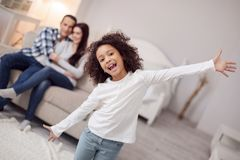 Content lovely girl spreading her arms. Relaxation. Beautiful alert curly-haired girl smiling and spreading her arms and her sitting on the couch in the Royalty Free Stock Photography