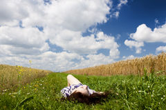 Relaxation. Beautiful young girl resting in a meadow under a cloudy sky Royalty Free Stock Images