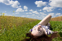 Relaxation. Beautiful young girl resting in a meadow under a cloudy sky Stock Photography
