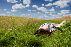 Relaxation. Beautiful young girl resting in a meadow under a cloudy sky Stock Photos